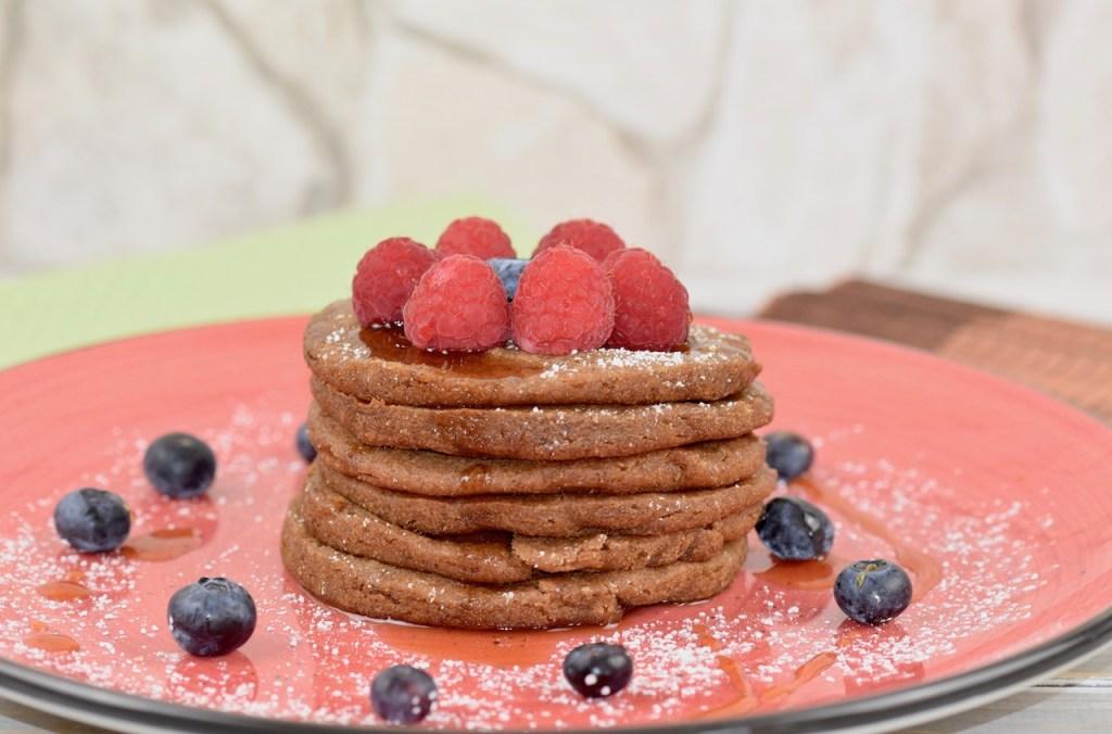 Glutenfreie Pfannkuchen gestapelt auf roten Teller, garniert mit Himbeeren, Blaubeeren, Ahornsirup und Puderzucker. Hintergrund hell.