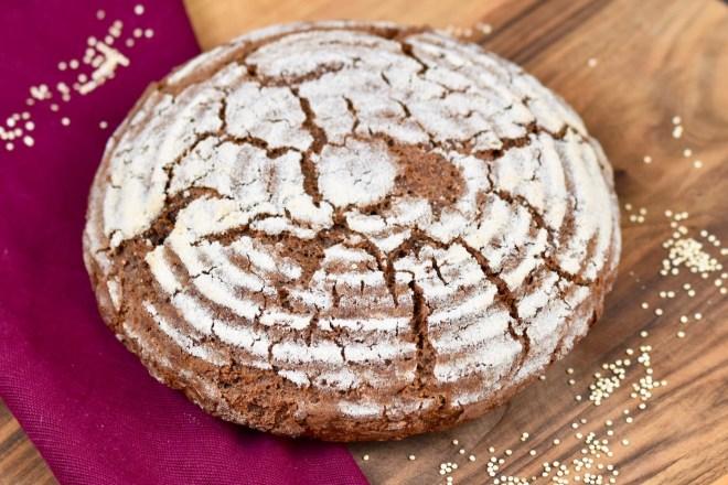 glutenfreies Krustenbrot in rund auf Holzbrett. Dekoriert ist es mit einer weinroten Stoffserviette und groben Salzkörnern.