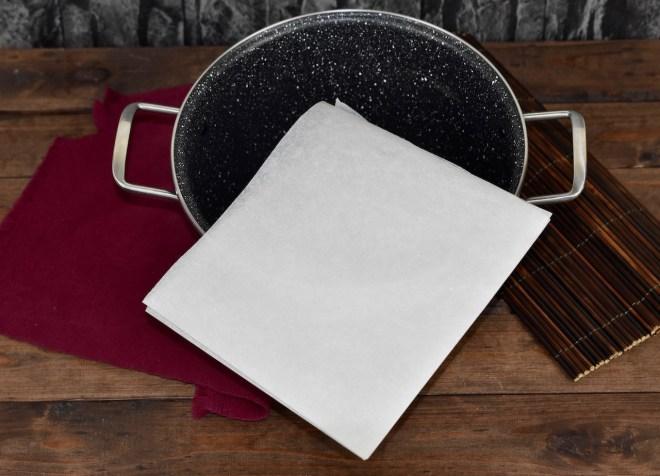 Ein Blatt weißes Backpapier 2 mal gefaltet. Eine Spitze mittig über einen Topf gelegt. Hintergrund dunkel.