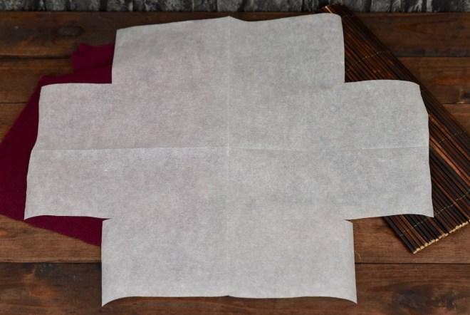 Das eingeschnittene Backpapier ist aufgefaltet. Es sieht aus wie ein dickes Kreuz. Hintergrund dunkel.