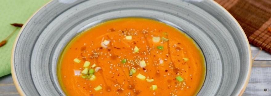 Karottensuppe mit Ingwer und Orange in grauem Teller. Garniert mit Sesamsamen, Sesamöl und Frühlingszwiebeln. Hintergrund hell.
