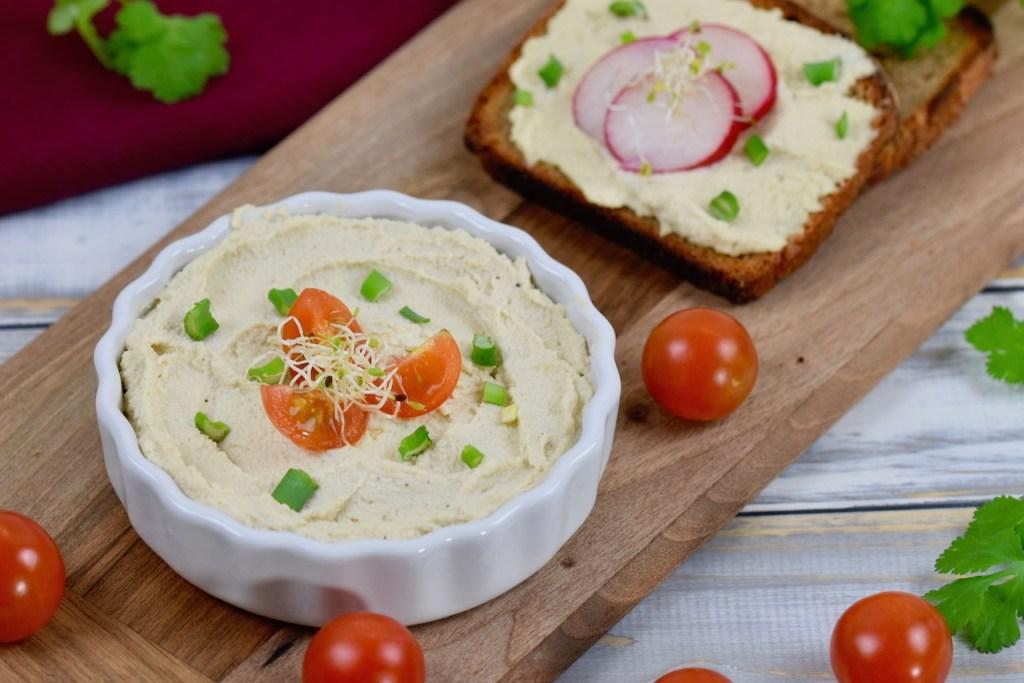 Veganer Frischkäse in weißer Schale, die auf einem Holzbrettchen steht. Der Frischkäse ist mit Vierteln von Cocktailtomaten, Frühlingszwiebel und Sprossen garniert. Im Hintergrund liegt eine Scheibe Brot mit Frischkäse und drei Scheiben Radieschen.