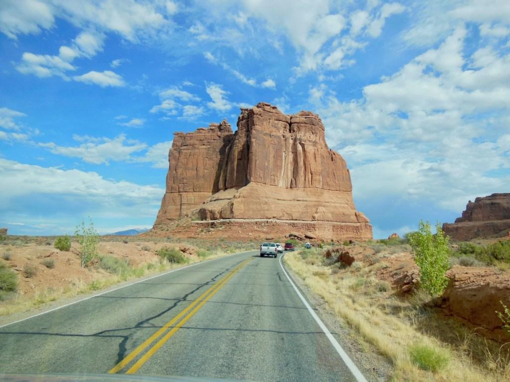 Straße vor einem großen roten Felsen, Arches NP - USA