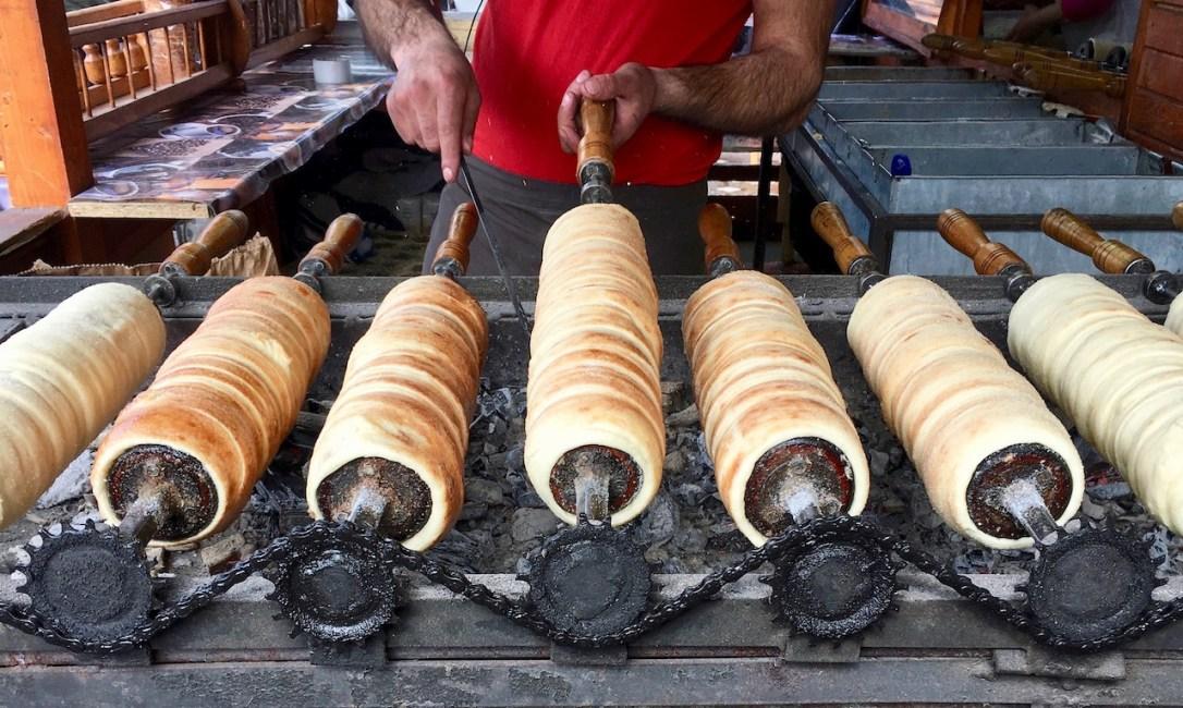 Foto für die 25 leckersten Gerichte: Kürtös Kalacs bzw. Baumstriezel auf langen runden Eisenformen über einem Holzkohlegrill