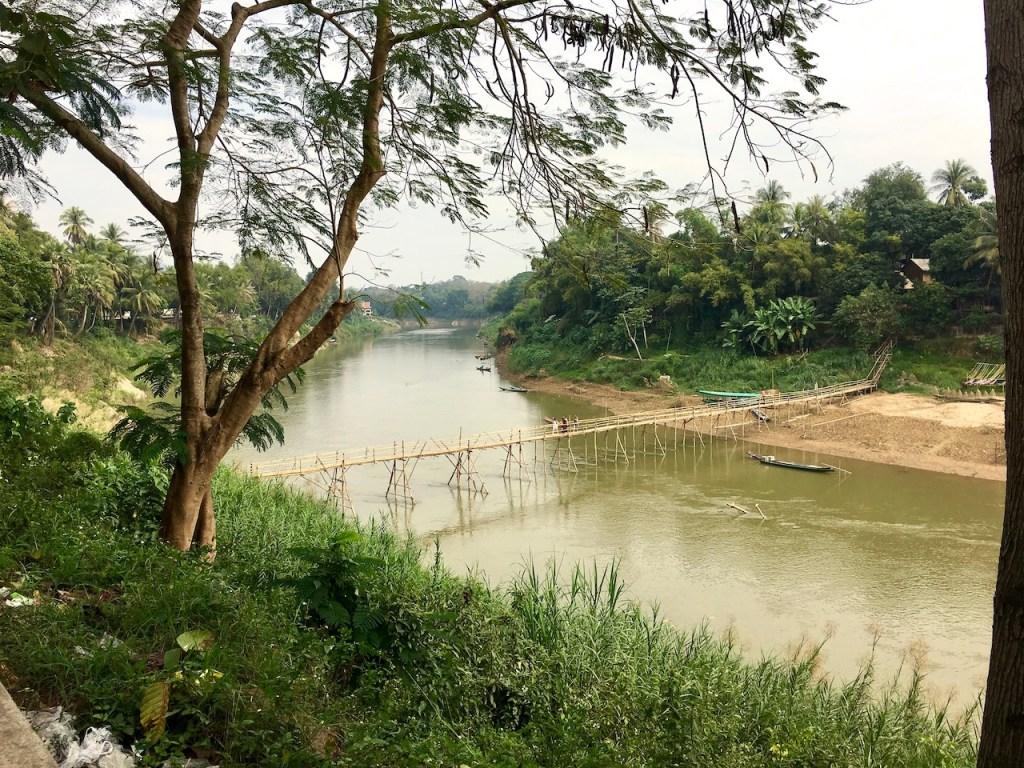 hölzerne Hängebrücke über einem Nebenfluss vom Mekong mit tropischer Vegetation in Luang Prabang - Laos