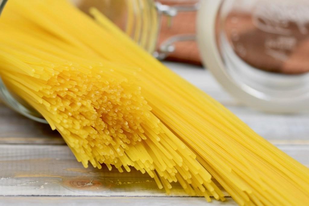 Spaghetti in einem Glas liegend. Die Spaghetti sind leicht aus dem Glas rausgerutscht. Hintergrund hell.