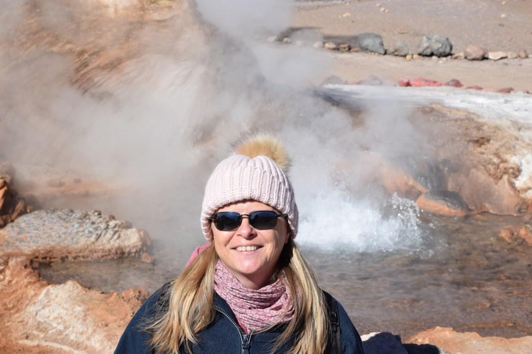 Über mich - Ich mit Mütze. Im Hintergrund sind ein Geysir und hellbraune Felsen