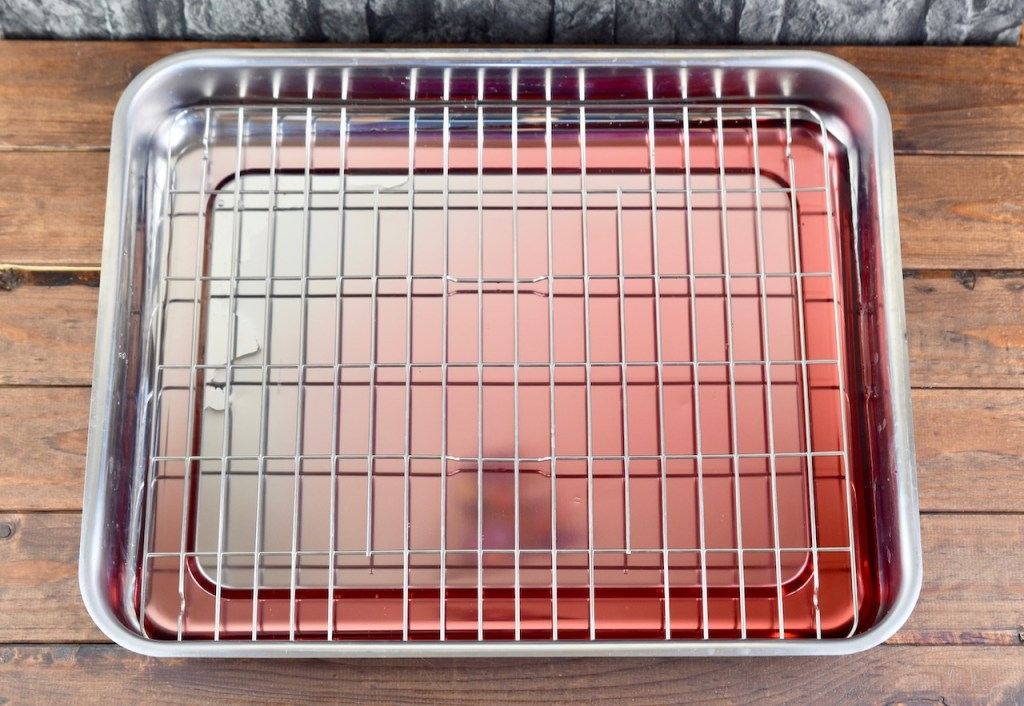 Schale mit Granatapfelsaft gefüllt und einem Gitter darüber um die Ribs zu dämpfen. Hintergrund dunkel
