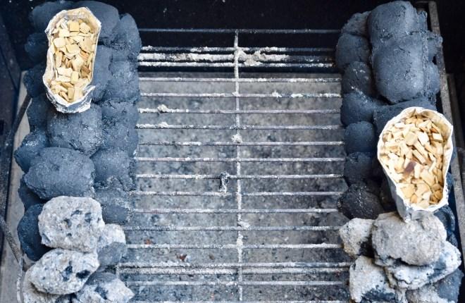 Holzkohlebriketts im Grill in Reihen aufgeschichtet. Obendrauf steht jeweils ein Aluschiffchen mit Räucher-Chips. An den Anfang wurden je 5 glühende Briketts gelegt.