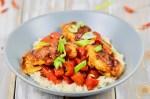 Gebackenes Hoisin-Hähnchen auf Paprikagemüse mit Reis in hellgrauem Teller. Der Teller steht auf einer weißen Holzfläche.