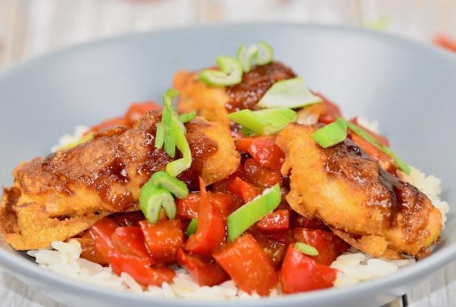 Gebackenes Hoisin-Hähnchen auf Paprikagemüse mit Reis in hellgrauem Teller. Nahaufnahme.