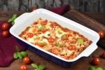Gnocchi-Auflauf in cremiger Tomatensauce mit Pilzen und Cocktailtomaten in einer Auflaufform. Hintergrund dunkel.