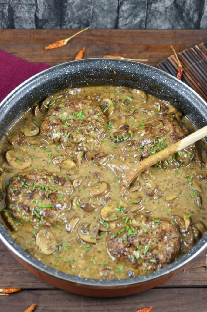 Frikadellen aus dem Backofen in cremiger Pilzsauce in einer tiefen Pfanne. Hintergrund dunkel.