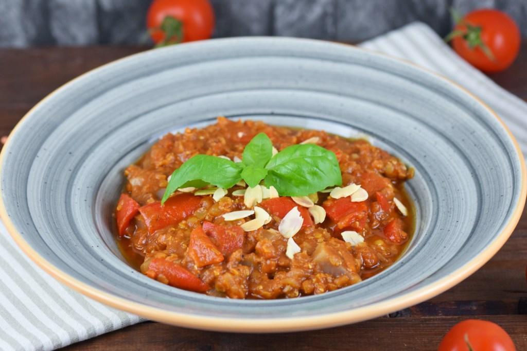 Italienischer Eintopf mit Tomaten, Paprika und Linsen in grauem Teller. Hintergrund dunkel.
