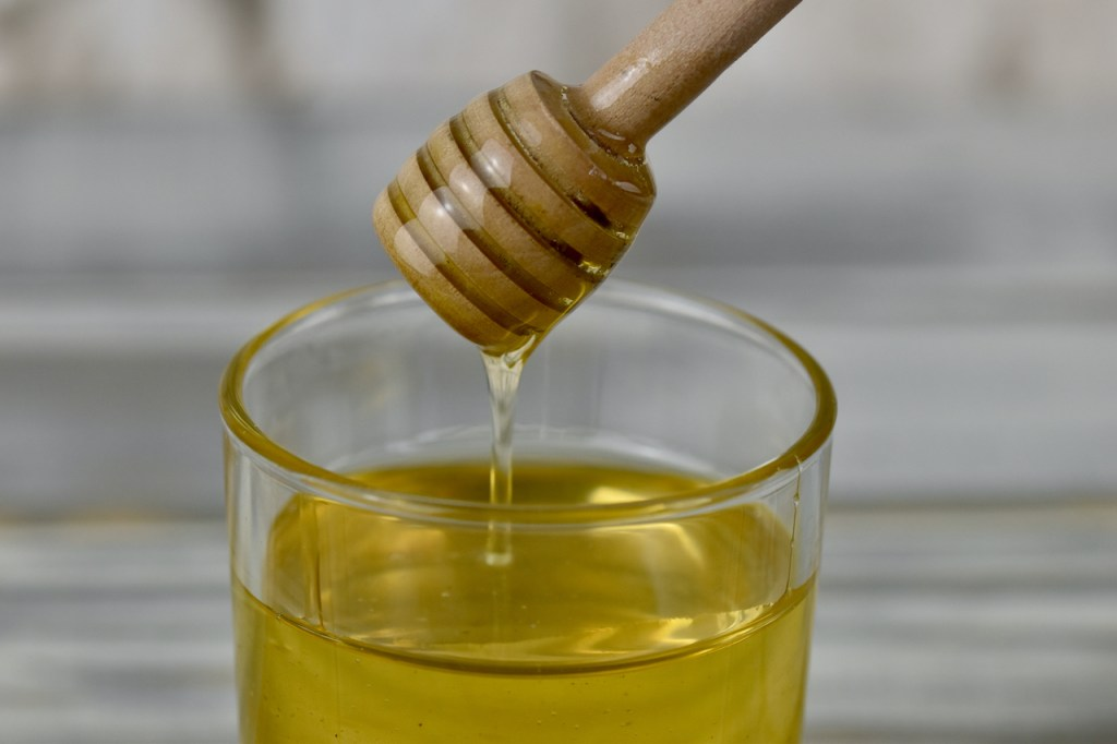 Honig in einem Glas mit Honiglöffel aus Holz.