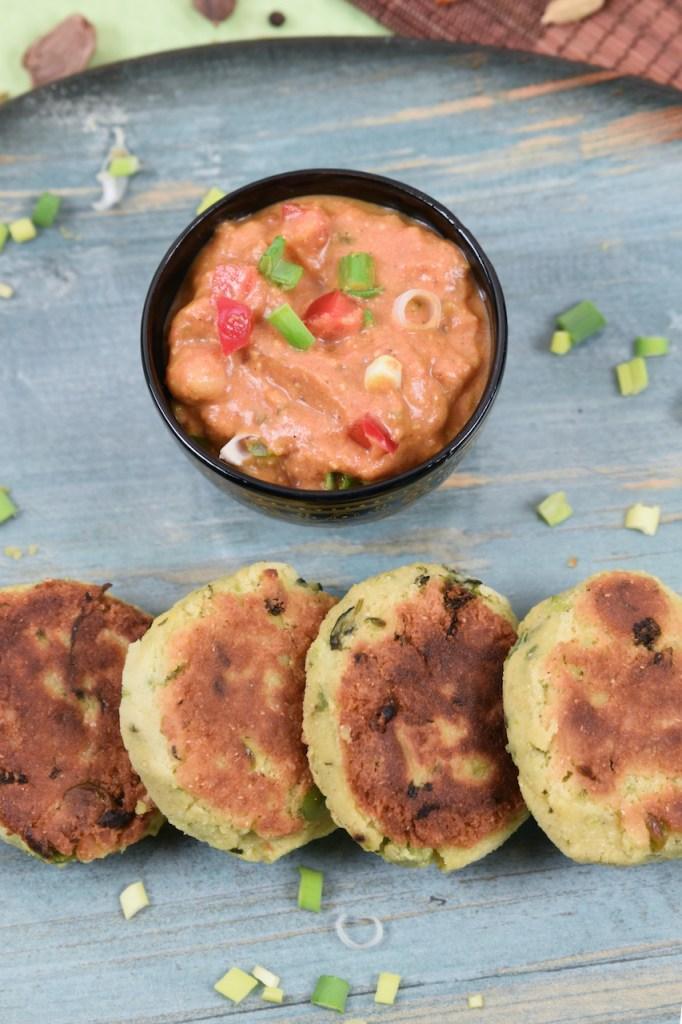 Indische Kartoffelküchlein auf blauem Teller. Dahinter steht eine Schale mit Kichererbsen-Curry.
