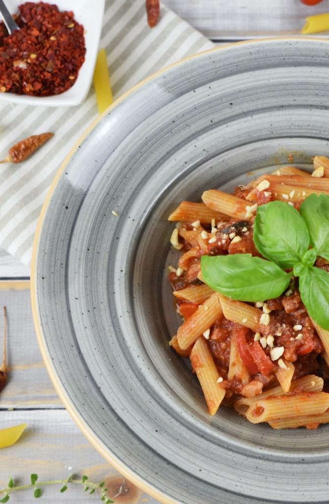 Penne Arrabiata mit Paprika und Oliven auf einem grauen Teller. Der Teller ist nur halb zu sehen. Hintergrund hell.
