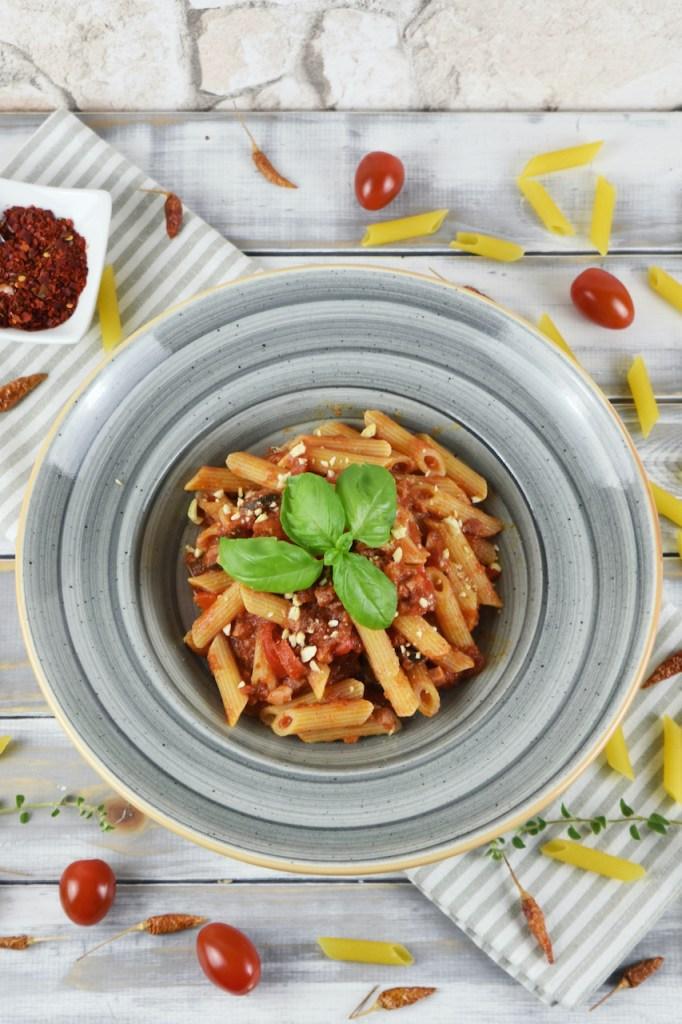 Penne Arrabiata mit Paprika und Oliven auf einem grauen Teller. Hintergrund hell.