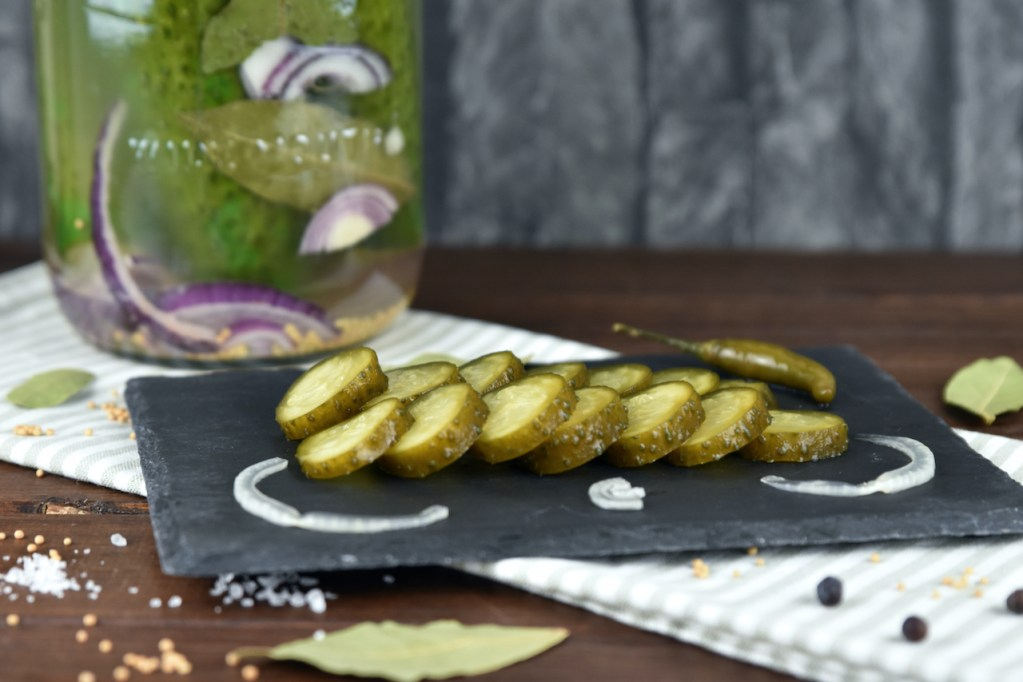 Fermentierte Gurken in einem Einmachglas. Davor liegen die Senfgurken angeschnitten auf einer Schieferplatte.