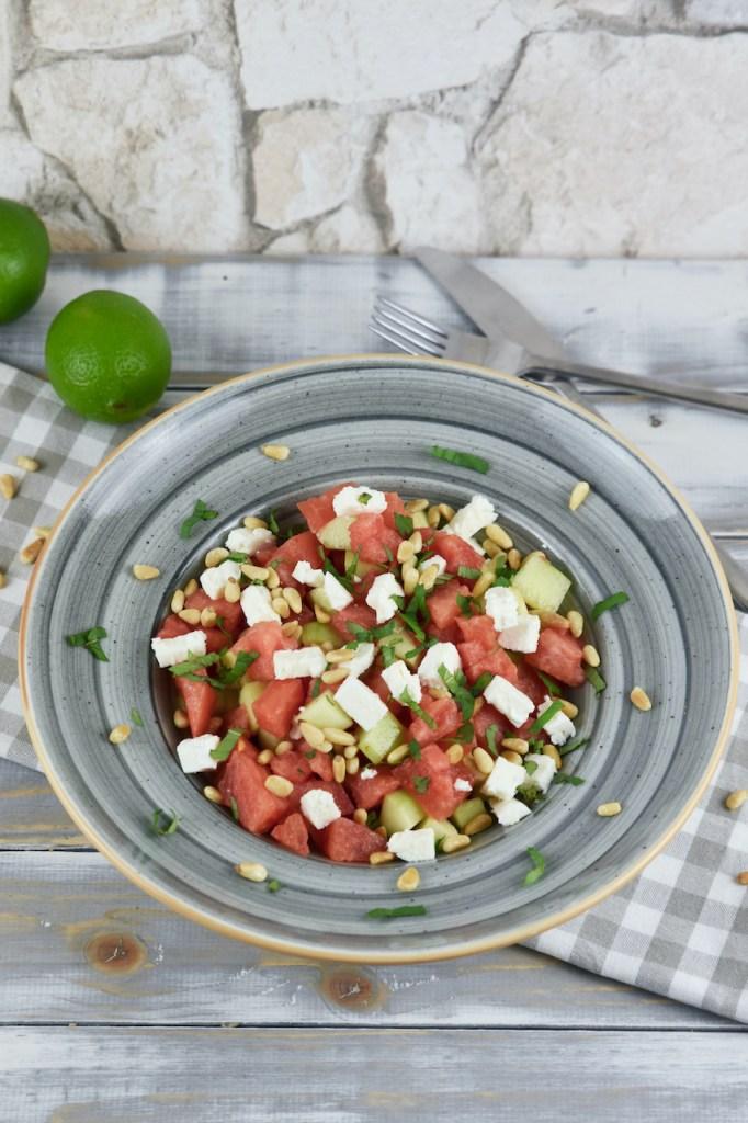 Wassermelonen-Feta-Salat iauf einem grauen Teller. Hintergrund hell.
