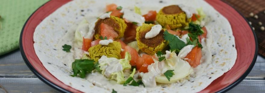 Falafel Wrap mit Gemüse, Salat und Sauce. Noch nicht aufgerollt.