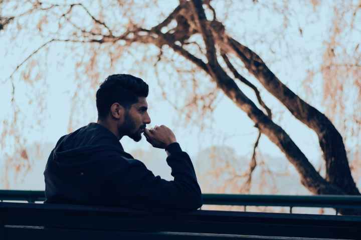 hindi poem loneliness cover image. man in black hoodie sitting on bench near green trees