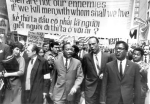 Dr. Martin Luther King talks to Al Raby of Chicago's Coordinating Council of Community Organizations (CCCO) as they lead the march down State Street. To King's right is Jack Spiegel of the United Shoeworkers, and to Raby's left is King assistant Bernard Lee. Photo: Jo Freeman.