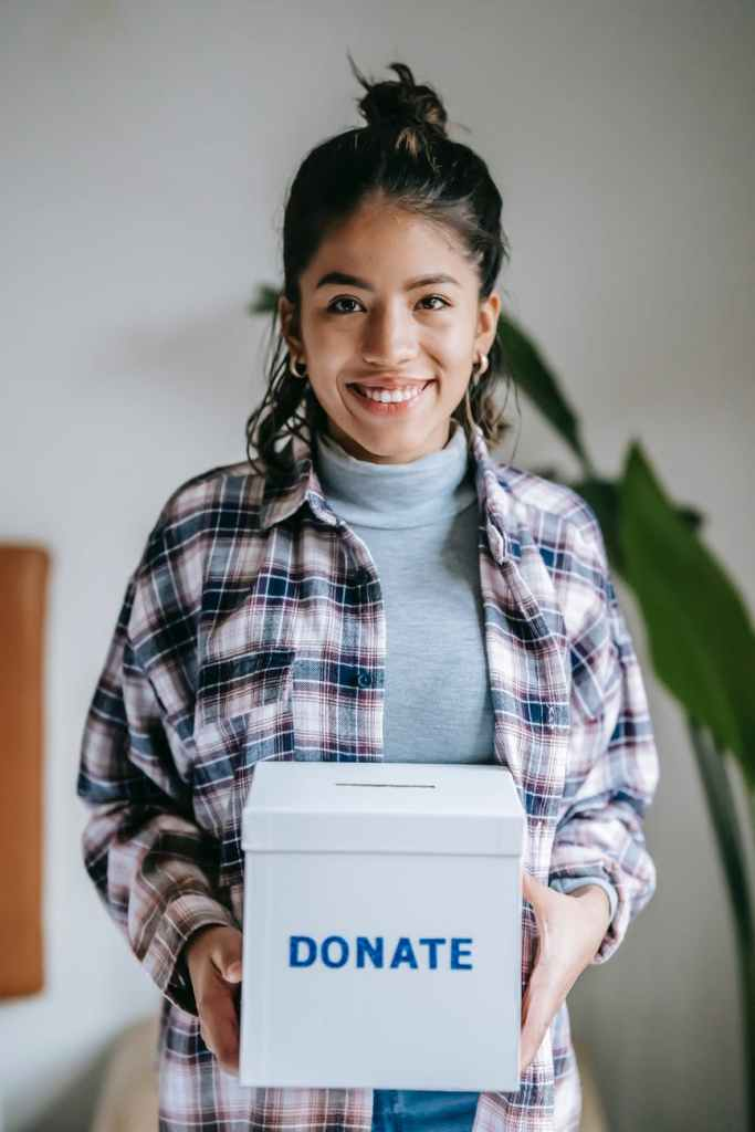 cheerful ethnic woman with donate box