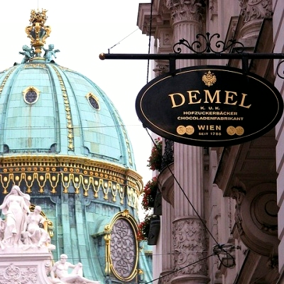 Demel cafe sign and Hofburg dome Vienna Austria
