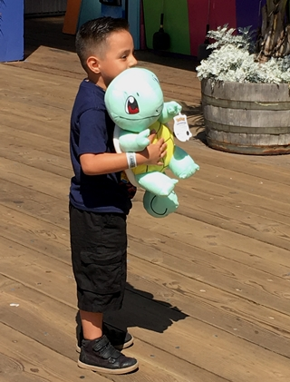Little boy with prize stuffed toy Santa Monica pier California
