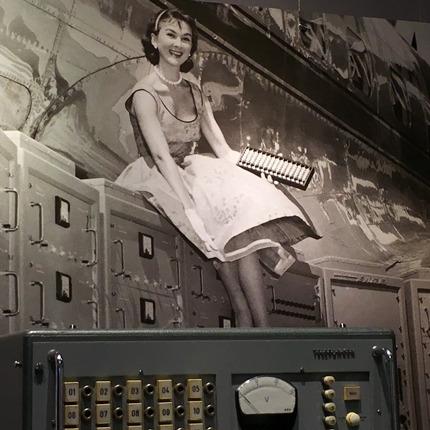 Woman with abacus sitting atop mainframe Computer History Museum