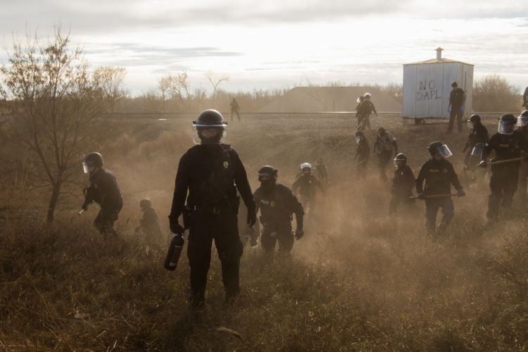 Premiul I Categoria Contemporary Issues Story © Amber Bracken  Title: Standing Rock: Morton County Sheriffs - Riot police clear marchers from a secondary road outside a Dakota Access Pipeline (DAPL) worker camp using rubber bullets, pepper spray, tasers and arrests. In other incidents they've employed militarized vehicles, water canons, tear gas and have been accused of using percussion grenades.