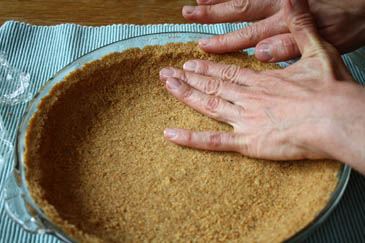 Pressing graham cracker crust into pie pan | ZoëBakes | Photo by Zoë François
