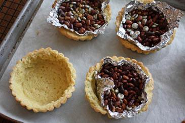 Weighing down tart dough in baking tins | ZoëBakes | Photo by Zoë François