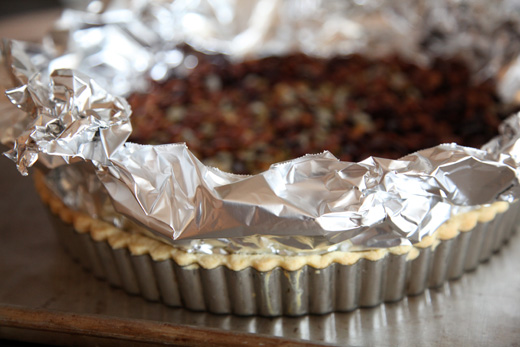 Almond tart dough in a tart pan ready for a blind bake