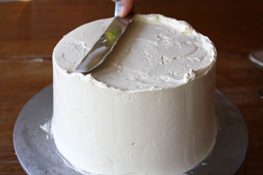 Smoothing buttercream on a layer cake.