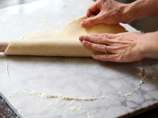 The best apple pie recipe - folding the dough over the rolling pin | photo by Zoë François