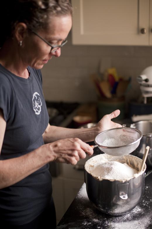Zoe sifting flour into a bowl of egg mixture | photo by Zoë François
