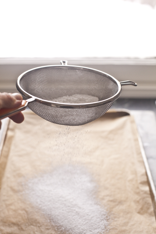 Dusting parchment with powdered sugar   how to make homemade marshmallows   photo by Zoë François