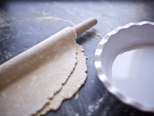 A circle of pie dough on a rolling pin next to an empty pie plate.