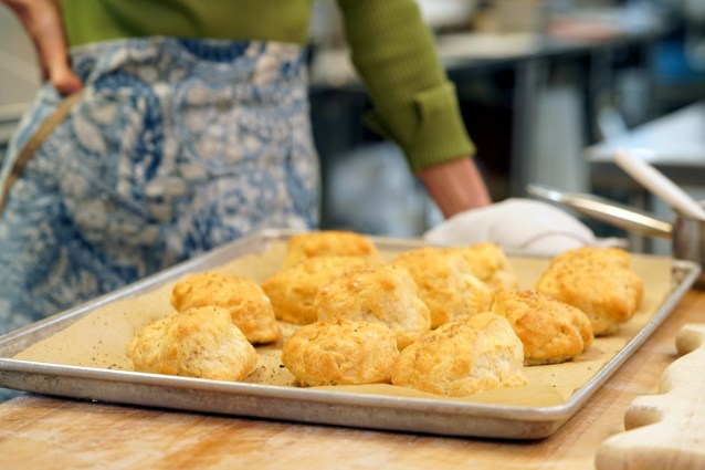 Zoë stands with a tray of biscuits made with Justin Sutherland at Handsome Hog on Zoë Bakes on Magnolia Network