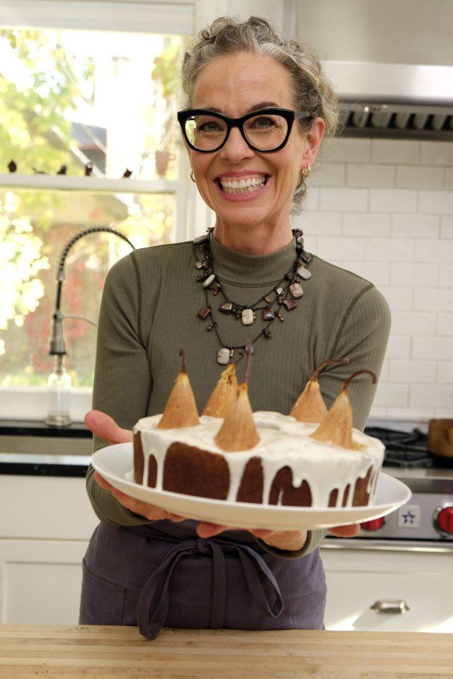 Host Zoe Francois with her pear cardamom cake, as seen on Zoe Bakes, season 1.