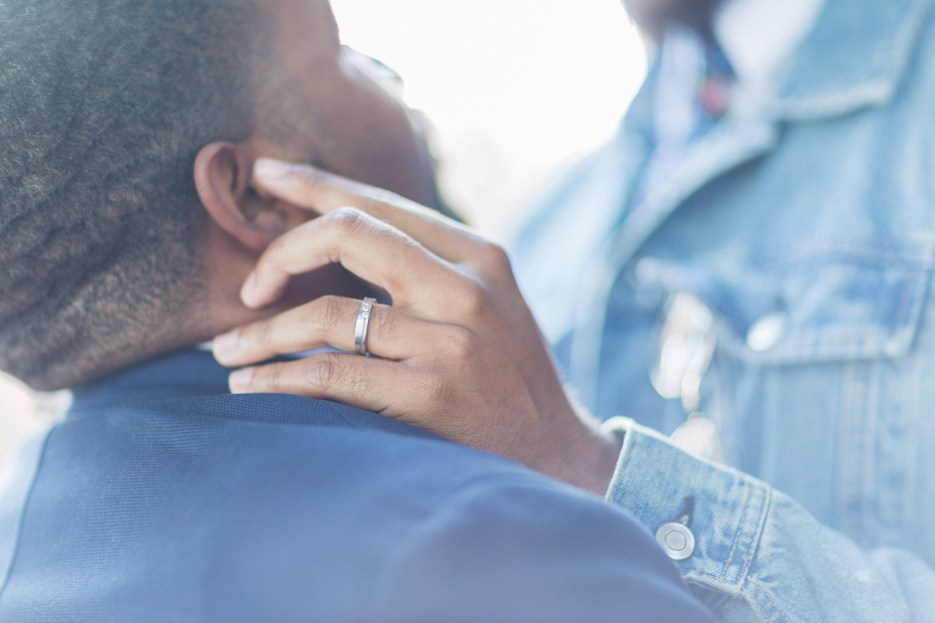 intimate tender moment at gay engagement photography session ring close up