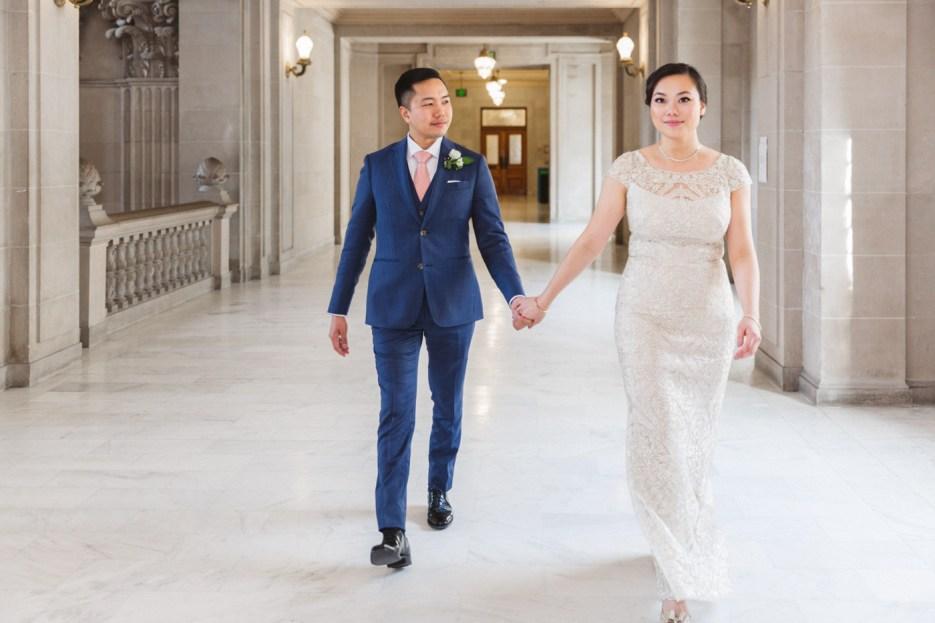 bride and groom walk along corridor in sf city hall