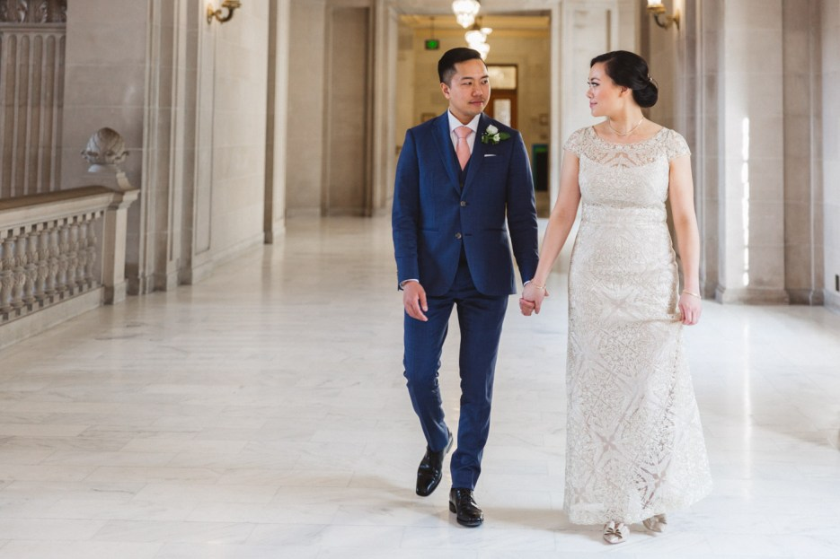 bride and groom face each other while walking