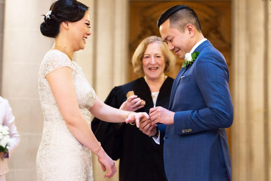 groom places ring on finger san francisco city hall