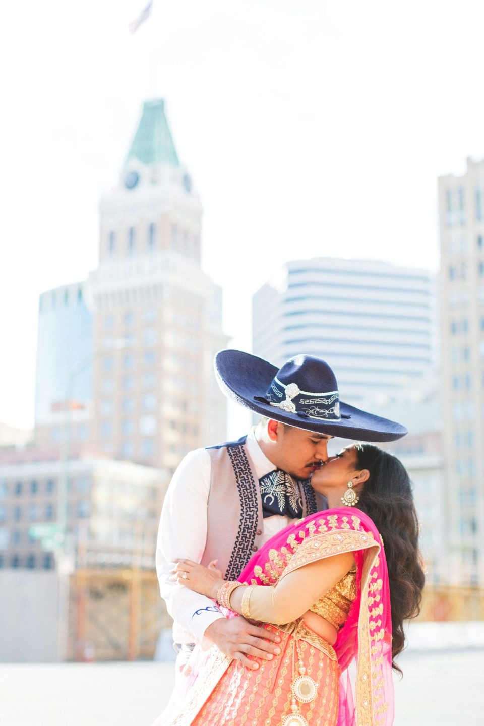 indian and mexican couple kissing in front of oakland tribune tower
