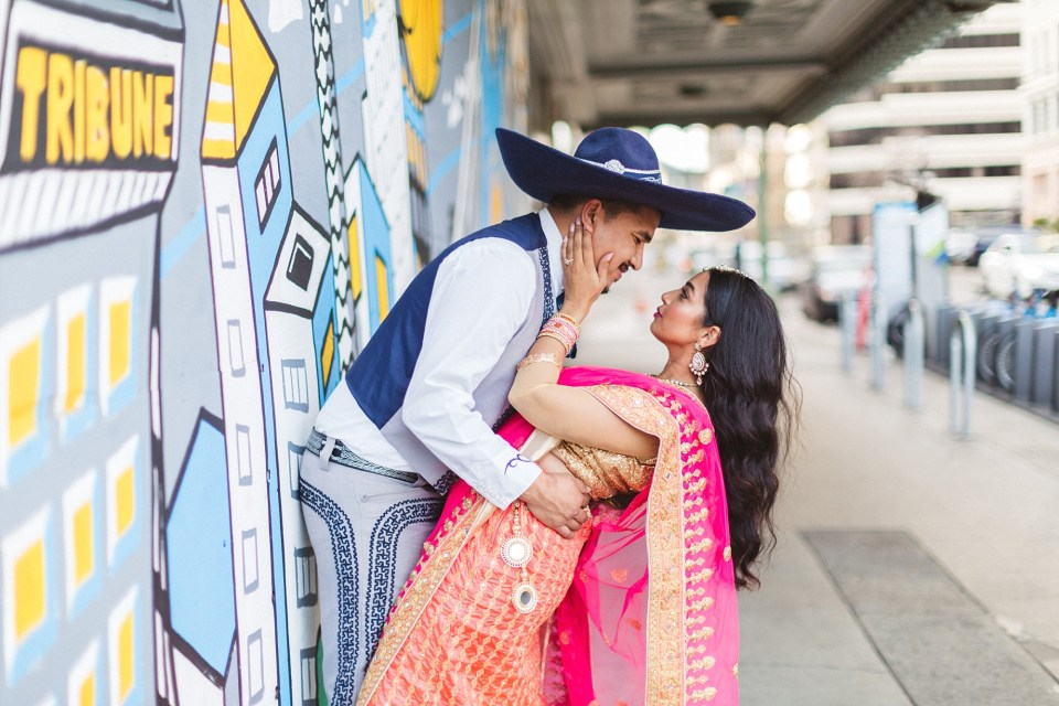 woman in pink indian dress kissing fiance in downtown oakland shoot