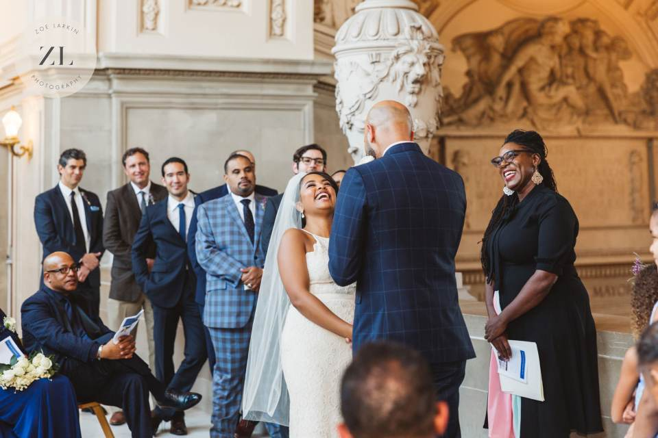 On The fourth floor of San Francisco City Hall, a couple has their wedding ceremony and the bride throws her head back laughing | Zoe Larkin Photography