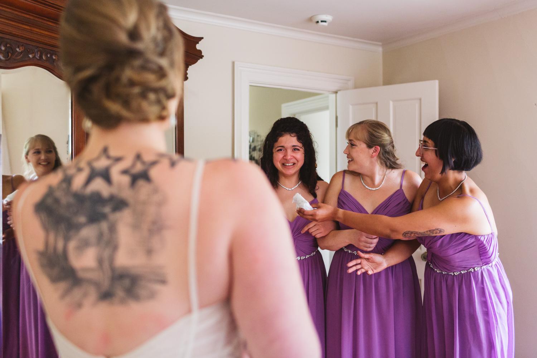 bridesmaids first look of bride in wedding dress